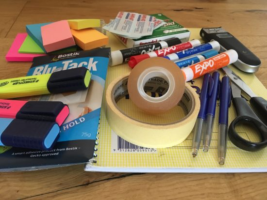 stationery spread out, including pens, highlighters, tape, paper and sticky notes