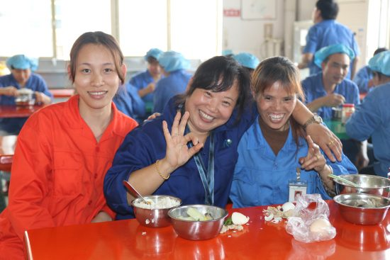 Three smiling Chinese ladies in a factory canteen.