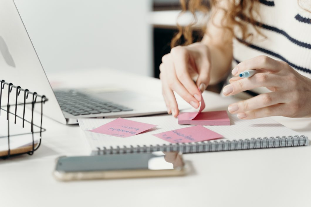 woman's hands picking up sticky notes on desk with laptop